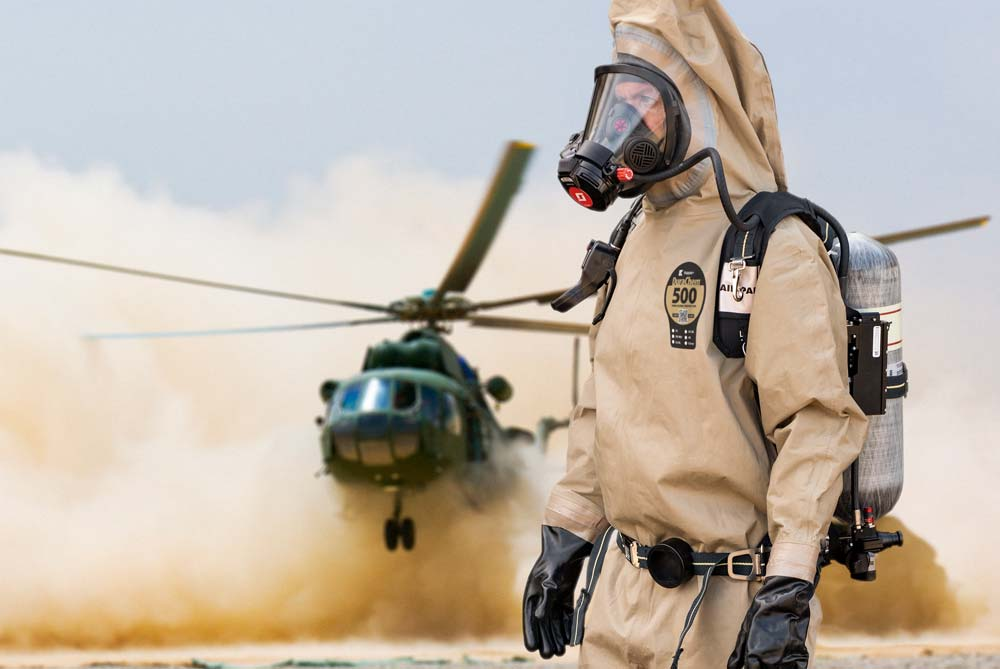 Military personnel in DuraChem 500 NFPA 1994 CBRN suit in front of landing helicopter