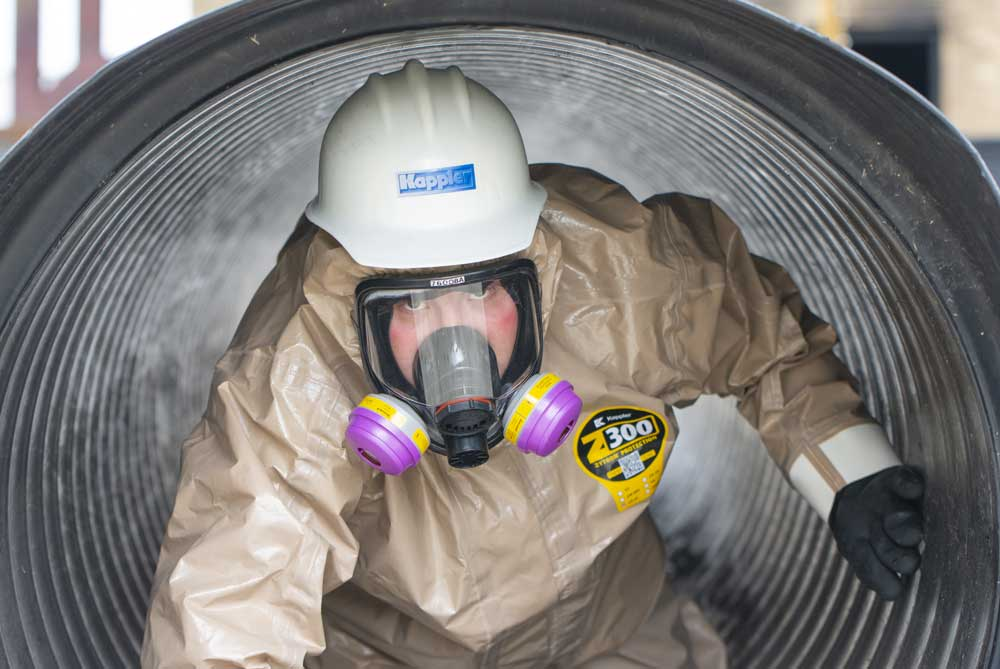 Worker in Zytron 300 suit emerging from a pipe after inspecting for chemical leaks